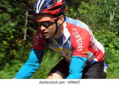 Athlete riding bicycle with motion background