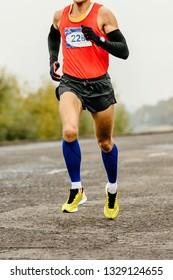 athlete runner in compression socks and arm sleeves runnning marathon