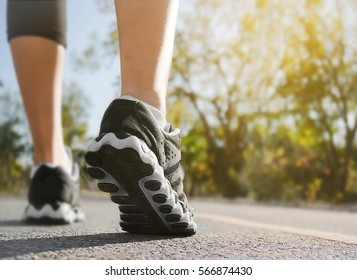 Athlete runner feet at the road, selective close up shoe with nature background. woman fitness sunrise jog workout.