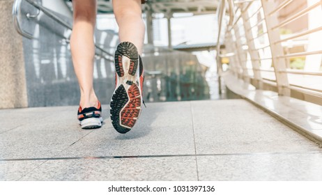 Athlete runner feet running in the city closeup on shoe. Sportsman fitness jog workout wellness concept. Man runner legs and shoes in action on road outdoors.
