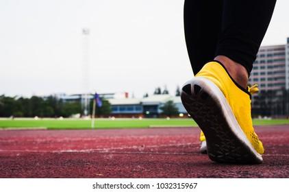 Athlete runner feet running on track closeup on shoe. woman fitness jog workout wellness concept.