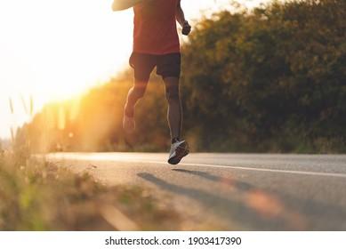 Athlete Läufer Füße laufen auf der Straße, Jogging-Konzept im Freien. Mann, der für Sport kandidiert.