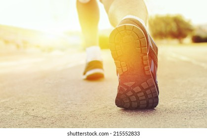 Athlete runner feet running on treadmill  closeup on shoe.Mans fitness with the sun effect of fall autumn colors in the background and open space around him