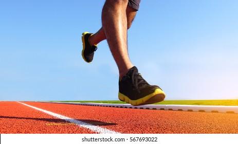 Athlete runner feet running on running track. Sport background