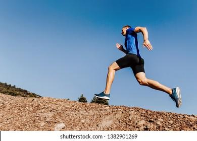 athlete runner run uphill trail on blue sky background