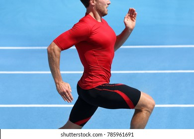 Athlete runner running on athletic track training cardio. Jogger man jogging fast pace for competition race on blue outdoor stadium tracks wearing red compression sport clothes. Male person fit body.
