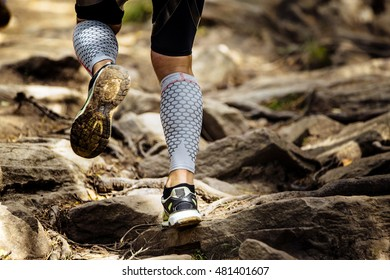 athlete runner runs rocks in mountain. closeup of legs compression socks and sneakers