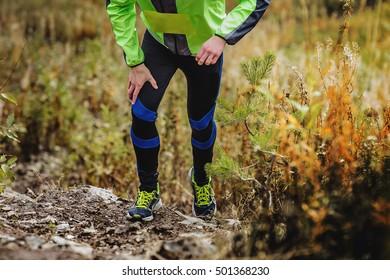 athlete runner skyrunners running uphill on autumn trail of mud and stones