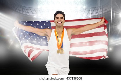 Athlete running with gold medals and American flag after victory against an arena