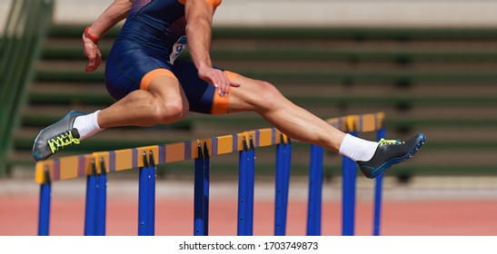 Athlete running a hurdle race in a stadium, runner jumping over an hurdle during track and field event