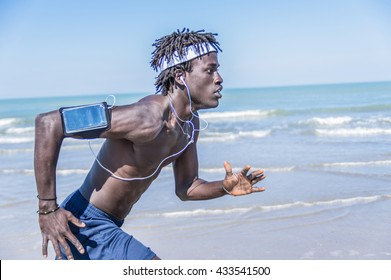 Athlete running man listening to music on smartphone. Sporty fit young man jogging at the beach