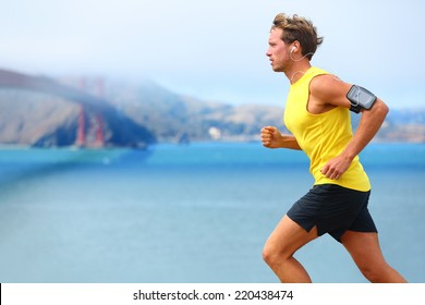 Athlete running man - male runner in San Francisco listening to music on smartphone. Sporty fit young man jogging by San Francisco Bay and Golden Gate Bridge. Jogger training with smart phone armband,