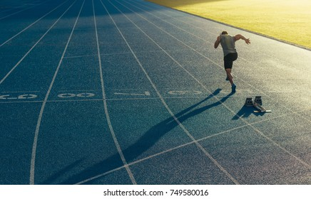 Athlete running on an all-weather running track alone. Runner sprinting on a blue rubberized running track starting off using a starting block.