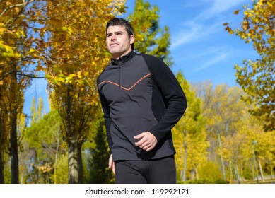 Athlete running on autumn park. Athlete exercising outdoors with trees on background.