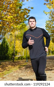 Athlete running on autumn park. Sportsman exercising outdoors with trees on background.