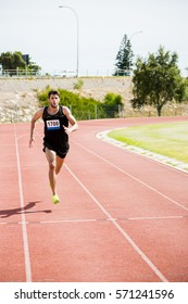 Athlete running on the racing track on a sunny day