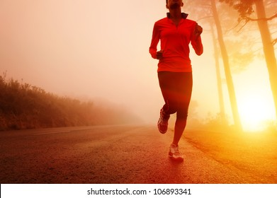 Athlete running on the road in morning sunrise training for marathon and fitness. Healthy active lifestyle latino woman exercising outdoors. Motion blur to show speed.