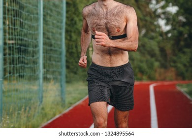 Athlete running on running track alone. Runner sprinting on a red rubberized running track starting off using a starting block. Man runnig with chest puller.