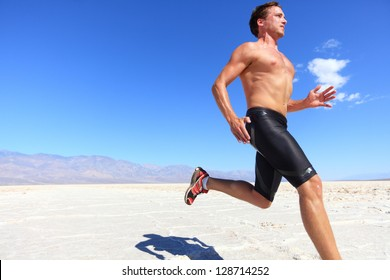Athlete running sport - fitness runner sprinting in desert shirtless. Fit sports model man during sprint run at great speed under burning sun.