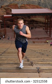 Athlete running up stairs at an outdoor amphitheater