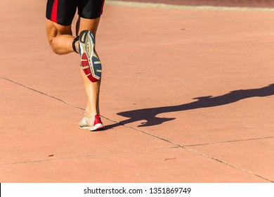 Athlete runnning rear behind legs feet shoes close-up abstract photo on concrete foot path.