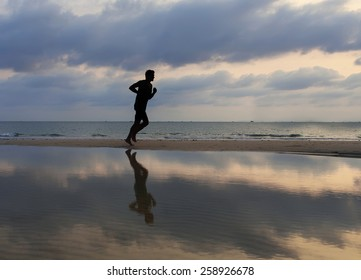 athlete runs along the sand beach with mirror on the water and o