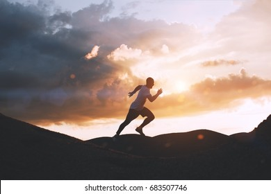 Athlete runs quickly through the hills outdoors at sunset. Healthy lifestyle concept