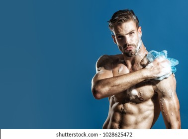 Athlete with serious faces washing body with sponge. Skin care, spa, beauty, people concept - handsome sexy macho, unshaven man taking shower. Advertising for men's cosmetics for body care. Copy space