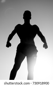 Athlete showing muscular body in dusk. Sportsman relaxing muscles, biceps, triceps. Silhouette of strong man. Fitness and sport concept. Bodybuilder posing on sky and sun light, black and white