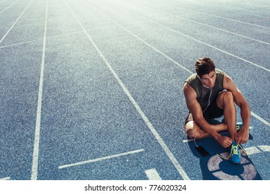 Athlete sitting on a running track tying shoe lace while listening to music. Runner wearing earphones sitting at the start line on the running track.