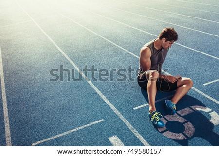 Athlete Sitting On Running Track Listening Stock Photo (Edit