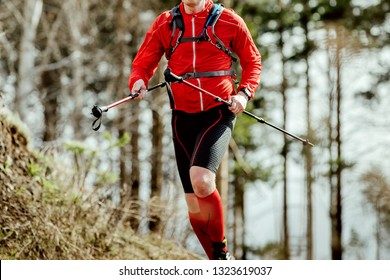 athlete skyrunner with trekking poles in hands running uphill in forest