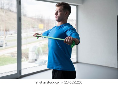 Athlete in Sport Sportswear Workout With Elastic Resistance Band - Doing Shoulder Or Back Exercises in Gym