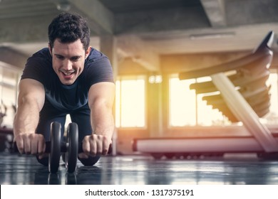 Athlete sporty man doing exercise with abs roller wheel to strengthen his abdominal muscle in gym.