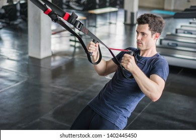 Athlete sporty man doing exercise with fitness trx straps to strengthen his abdominal muscle in gym.