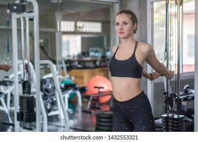 Athlete sporty woman doing exercise with fitness trx straps to strengthen his abdominal muscle in gym.