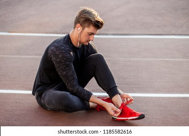 Athlete sprinter getting ready to run tying shoe laces while sitting on race track on stadium