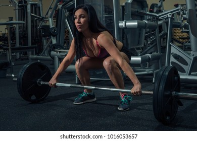 Athlete squats with a barbell in the gym. Sport life