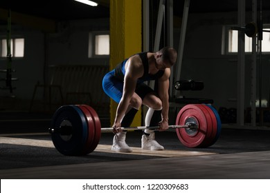 Athlete Is Standing on His Knee and Near the Bar in the Gym and Is Preparing to Make a Deadlift