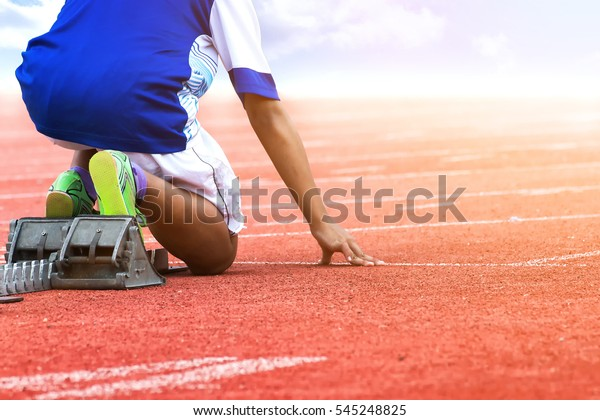 Athlete in the starting block waiting for the start in running track