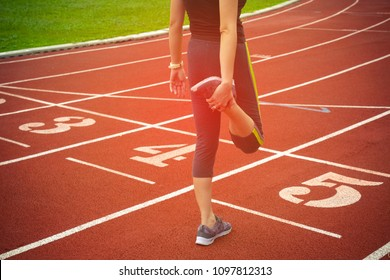 The athlete stretches the line before starting blocks on the running track.