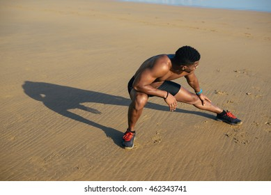 Athlete stretching adductor and hamstring after running at the beach. Black runner exercising and warming up before workout outdoor.
