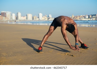 Athlete stretching hamstring and back before running at city beach. Black runner exercising and warming up for outdoor summer workout. Gijon, Asturias, Spain.
