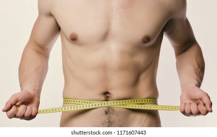 Athlete with strong muscles measures waist or sixpacks. Guy with nude chest on white background. Man with long yellow measuring tape around naked torso. Measurement and sports lifestyle concept.