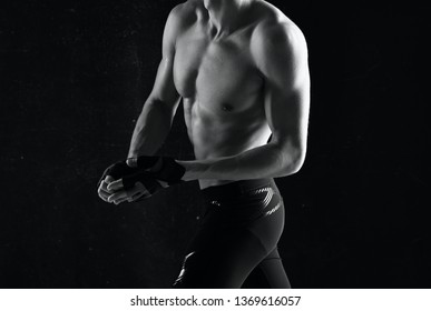 Athlete with a strong torso and black leggings on a dark background