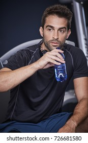 Athlete taking a drink in gym, looking away