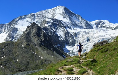 Athlete trail running in the beautiful mountains of Arolla, Switzerland. Sports and healthy lifestyle concept.