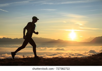 Athlete trailrunning in the mountains during a nice sunrise.