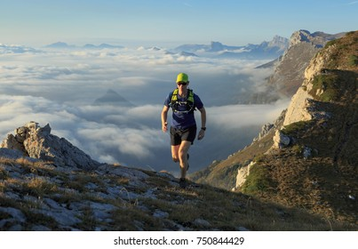 Athlete trailrunning in the mountains on a beautiful morning. Les Vercors, France.