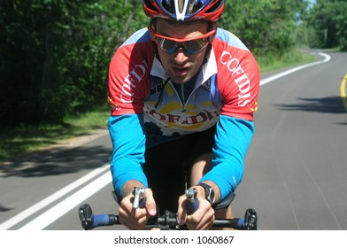 Athlete training by riding his bicycle on country road
